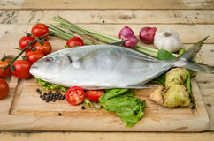 Fish and vegetables on kitchen board Stock Photo