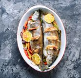 Trout with bacon and vegetables. Fish with vegetables and lemon.Delicious trout fishes baked with bacon royalty free stock photo