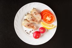 Fish and vegetables on white plate. Uncooked isolated ingredients on black background. Top view. Copy space.  Royalty Free Stock Photography