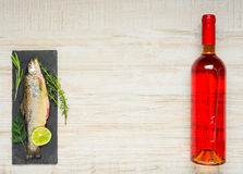 Fish and Wine with Copy Space. Copy Space Area with Rainbow Trout Fish and Rose Bottle Wine royalty free stock photos