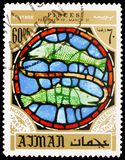 Fish, zodiac sign in the Notre Dame Cathedral, Paris, serie, circa 1971. MOSCOW, RUSSIA - MAY 25, 2019: Postage stamp printed in Ajman shows Fish, zodiac sign in stock image