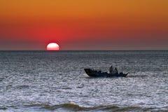 Fishboat på solnedgången över havet Arkivfoto