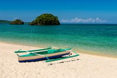 Fishboat on sand and two small islands on tropic turquoise sea Stock Images