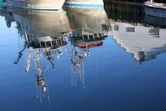 Fishboats and Cannery Reflection. The reflection of fishing seiners tied up outside the Gulf of Georgia Cannery National Historic Site in Steveston, British Stock Photos