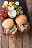 Fishburger用鲱鱼、小汤和新鲜蔬菜特写镜头 Ve 免版税库存图片