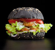 Fishburger. Black bun with a fish cutlet, salad and a squid on a black background Royalty Free Stock Image