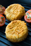 Fishcakes. Two fish cakes on metal hot grill with tomatoes royalty free stock image