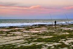 Pescador con la caña de pescar en la playa Foto de archivo
