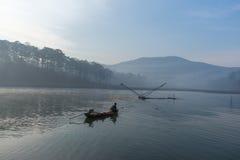 Fisher人鱼在湖渔夫人的工具,他们使用这一个为他们的工作,在有雾 库存图片