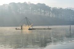 Fisher人鱼在湖渔夫人的工具,他们使用这一个为他们的工作,在有雾 免版税库存照片