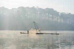 Fisher人鱼在湖渔夫人的工具,他们使用这一个为他们的工作,在有雾 库存照片