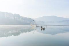 Fisher人鱼在湖渔夫人的工具,他们使用这一个为他们的工作,在有雾 免版税库存图片