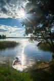 Fisher `简单的汽艇,被停泊对湖塞利格的岸边的森林在光芒四射的盲目的阳光下,俄罗斯 免版税库存图片