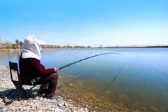 Fisher. Fishing on the lakeshore Royalty Free Stock Image