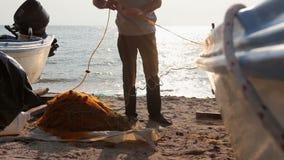 Fisher accatasta la rete da pesca su alla spiaggia sabbiosa stock footage