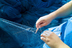 Fisher with blue fishnet. A fisher repair blue fishnet Royalty Free Stock Photo