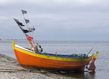 Fisher boat. Orange fisher boat on the seashore Royalty Free Stock Photography