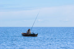 Fisher in boat at Baikal. Fisher with rods in boat at Baikal stock image