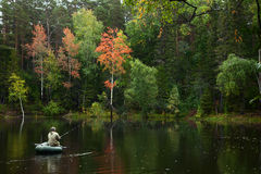 Fisher in boat is on the forest lake in autumn Stock Photos