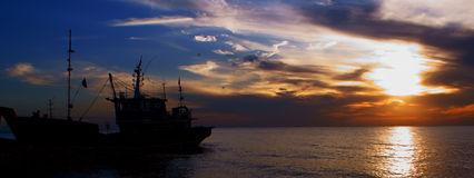 Fisher boat at sunset. The natural scenery include ships and sky near the beach in sunset stock images