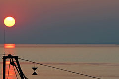 Fisher boat in sunset on the horizon above sea Stock Images