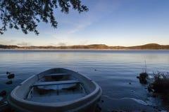 Fishing boat at sunrise at Inari lake, Finland Royalty Free Stock Photos