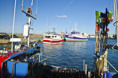Fisher boats in Joinville port in Yeu Island. Articles and parts of fisher boat are at foreground and two vessels at background, France, Vendee, Pay de la Royalty Free Stock Images