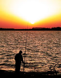 Fisher Boy 1. Scene of a boy silhouette fishing in the lake at sunset Royalty Free Stock Photo