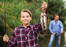 Fisher boy showing catch fish. Portrait of cheerful ad teenager boy showing catch fish he holding in hands stock photos