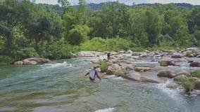 Fisher Carries Net med fisken på skuldra över floden lager videofilmer