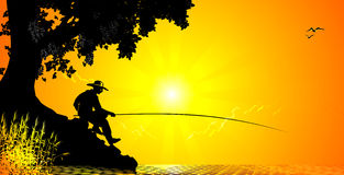 Fisher catches a fish on sunset background Stock Photo