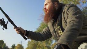 Fisher com pesca longa da barba no banco de rio Pescador que espera emocionalmente os peixes Pesca do rio filme