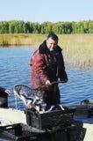 Fisher con il coregonus della cattura di pesce fotografia stock