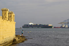 Fisher and container ship, Malta Royalty Free Stock Photography