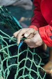 Fisher darning fish seine with net needle. Fisher darning fish seine with needle Stock Photo