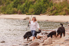 Fisher with dogs. Woman with her dogs on sea beach walking Royalty Free Stock Image