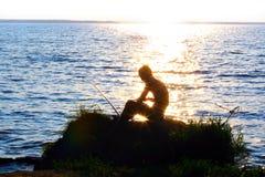 Fisher em um por do sol Imagem de Stock