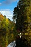 Fisher en barco está en el lago del bosque en otoño Foto de archivo libre de regalías