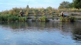 2 Fisher equipam com os peixes de travamento da vara de pesca no lago vídeos de arquivo