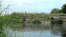 2 Fisher equipam com os peixes de travamento da vara de pesca no lago filme