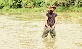 Fisher with fishing equipment. Fishing masculine hobby. Brutal man wear rubber boots stand in river water. Fun of