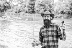 Fisher fishing equipment. Rest and recreation. Fish on hook. Brutal man stand in river water. Man bearded fisher. Fisher