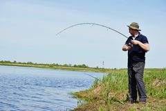 Fisher fishing fish with rod Stock Photo