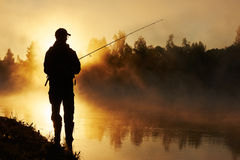 Fisher fishing on foggy sunrise. Fisher man fishing with spinning rod on a river bank at misty foggy sunrise Stock Image