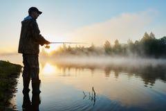 Fisher fishing on foggy sunrise Stock Photos