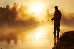 Fisher fishing on foggy sunrise Stock Photo