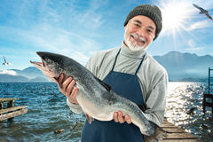 Fisher holding a big atlantic salmon fish. In the fishing harbor royalty free stock photography