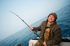 Fisher holds trolling rod. Stock Image