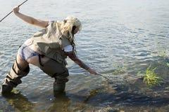 Fisher kvinna som fångar fisken fotografering för bildbyråer