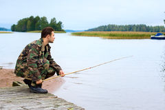Fisher on lake shore Royalty Free Stock Photos